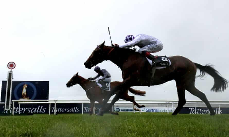 Mac Swiney ridden by Rory Cleary (left) is just ahead of Poetic Flare and Kevin Manning as they approach the finishing post in the Irish 2,000 Guineas at the Curragh.