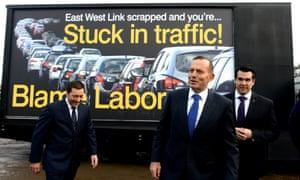 Victorian opposition leader Matthew Guy, Tony Abbott and local Liberal member Michael Sukkar in front of a billboard about the scrapped East West Link during a visit to Daisy's Garden Supplies in Ringwood, Melbourne, on Saturday.
