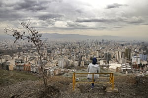 A woman looks out over the city as she observes the ancient festival of Sizdeh Bedar, an annual public picnic day on the 13th day of the Iranian new year.