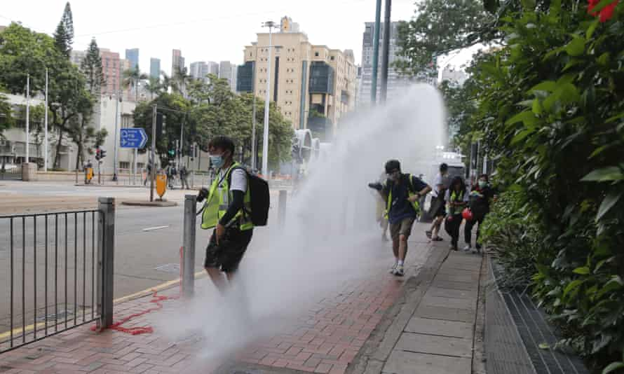 Journalists run as police fire a water cannon at marchers