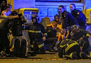 French fire brigade members aid an injured individual near the Bataclan concert hall following fatal shootings in Paris on 13 November 2015