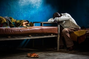 A man rests next to his bedridden wife, who is suffering from malaria, at the Saint Martyr health centre in Kananga