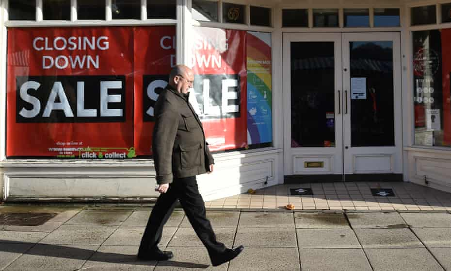A man walks past signs for a closing down sale in Newcastle-Under-Lyme, Staffordshire