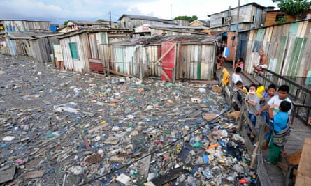 Residents of the Betania slum use a makeshift walkway to avoid garbage floating on floodwaters in Manaus.