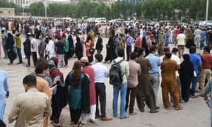People queue to receive a dose of a Covid vaccine in Karachi, Pakistan.