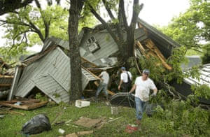People help salvage belongings from a house destroyed near Wimberley where the Blanco River rose 26 feet in an hour.