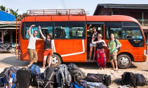 Backpackers wait for their tour bus to depart. Unloading at the last bus stop in southern Laos on the way to Don Det.