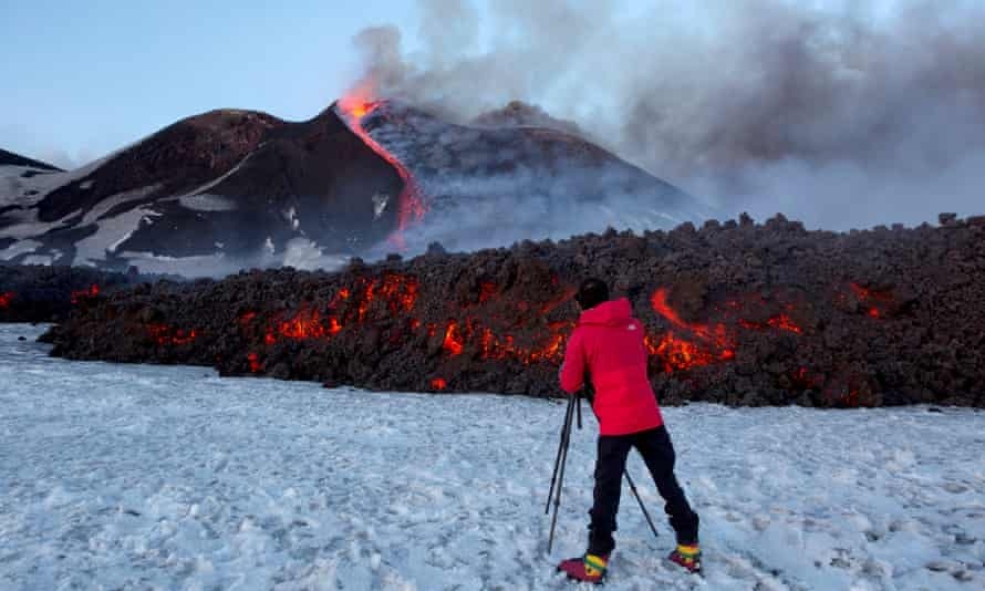 A tourist stands in front of Mount Etna on 28 February 2017 as it spews lava during an eruption.