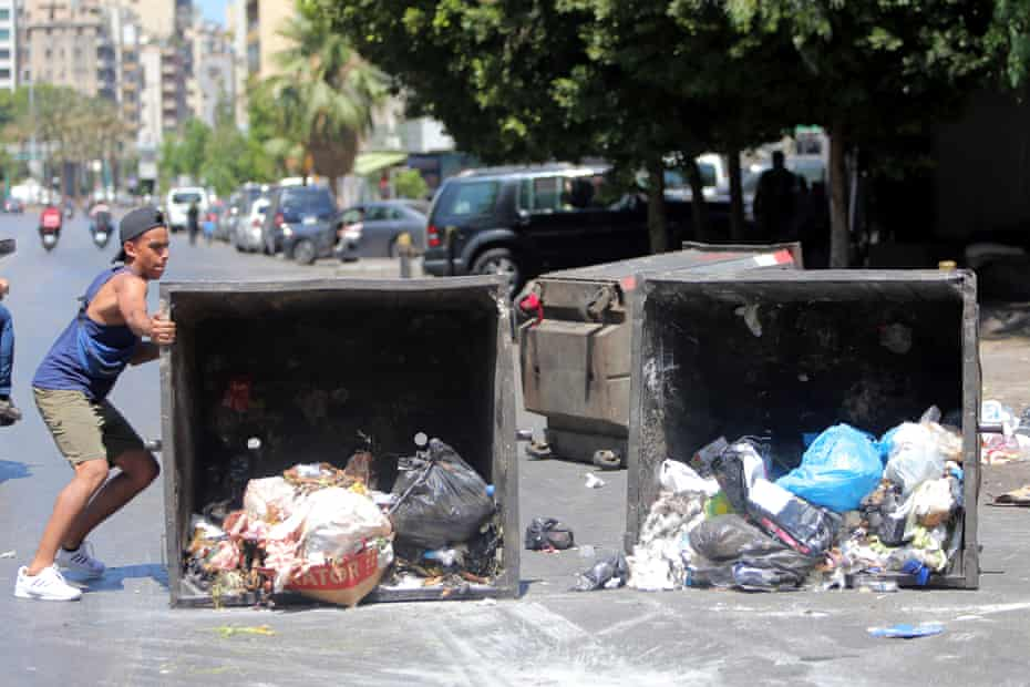 Protesters move a garbage container to block a main road in Beirut