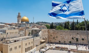 The Israeli flag flutters above the Western Wall in Jerusalem.