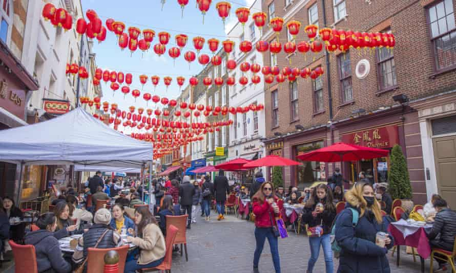 People dine in outdoor spaces in Chinatown in London.