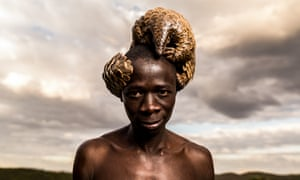 A man in Zimbabwe poses with a pangolin under his care at the The Tikki Hywood Trust. Today, the pangolin, which comprises eight species, is the world's most trafficked animal.