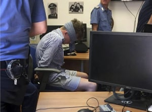 Gabriel Christian Natale Hjorth sits blindfolded in a police station in Rome.