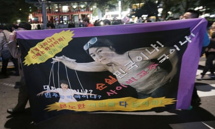 South Korean protesters carry a banner depicting President Park Geun-hye as a marionette and Choi Soon-sil as the puppeteer.