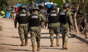 Members of the Mexican National Guard patrol in a refugee camp in Matamoros.