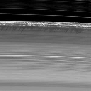 "26 July 2009 Vertical structures rise abruptly from the edge of Saturn's B ring to cast long shadows on the ring. These structures tower as high as 2.5 kilometers (1.6 miles) above the plane of the rings – a significant deviation from the height of the main A, B and C rings which are generally only about 10 meters (30 feet). It is believed large bodies, or moonlets, are responsible as they affect the material streaming past them, forcing the particles upward in a ""splashing"" manner. Images like this are only possible around the time of Saturn's equinox, which occurs about every 15 Earth years"