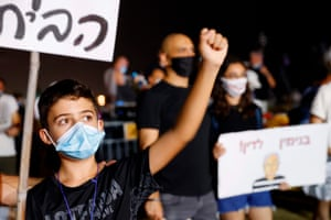 A boy raises his fist during a demonstration against the Israeli government in the Mediterranean coastal city of Tel Aviv on 1 August, 2020.