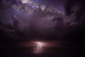 <strong>Calm Before the Storm</strong> A phenomenal natural light show of a lightning storm emanating from the underside of ominous storm clouds, juxtaposed with the gleaming stars of the Milky Way above