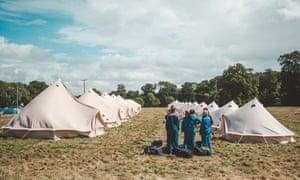 Festivalgoers in overalls prepare yurts.