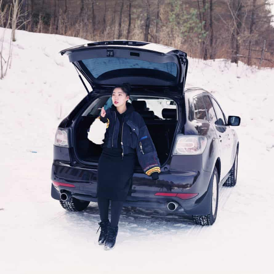 One of Chen's subjects, Ziyi, 22, stands in front of a car her parents bought her in Yichun, Heilongjiang province.