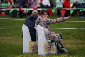 People sit on Pope-themed chairs ahead of the closing mass in Phoenix Park
