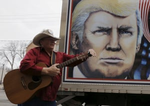 A man tunes his guitar before performing his song about Donald Trump in front of a truck featuring Trump in Des Moines, Iowa.