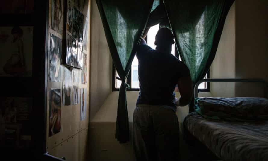 Man at a window in prison cell in semi-darkness