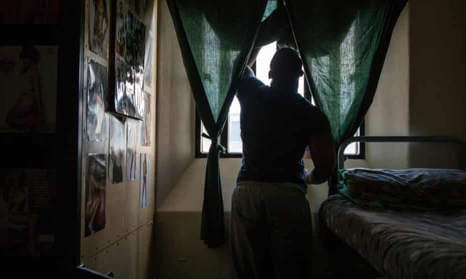 A prisoner stands at his cell window