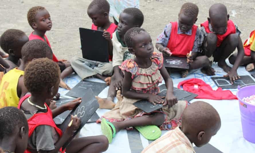 In the schoolyard at the Malakal protection of civilians camp children sketch on slates with chalk.