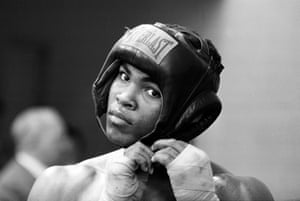 Cassius Clay adjusts the strap on his headgear during a training session at the Territorial Army drill hall in Shepherds Bush, London.