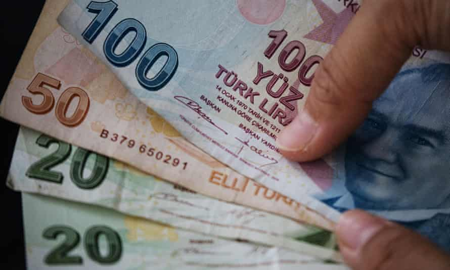A woman poses with Turkish Lira in Istanbul