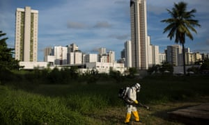 A municipal health worker sprays insecticide in an open area of a sports facility in Recife, Pernambuco state.