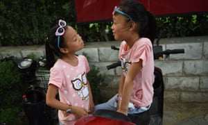 Two sisters play on electric scooter