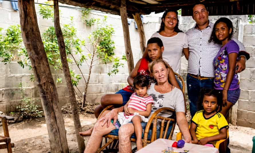 José Rafael (in the red top) supports his family, which has been devastated by Huntington's disease. Four generations live in the same house.