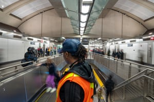 A transportation worker sprays disinfectant and wipes an escalator handrail at the 86th Street subway station in New York