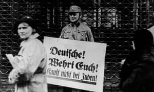 A Nazi soldier in Berlin holding a sign reading: 'Germans! Defend Yourselves!, Don't Buy From Jews!' in 1933.