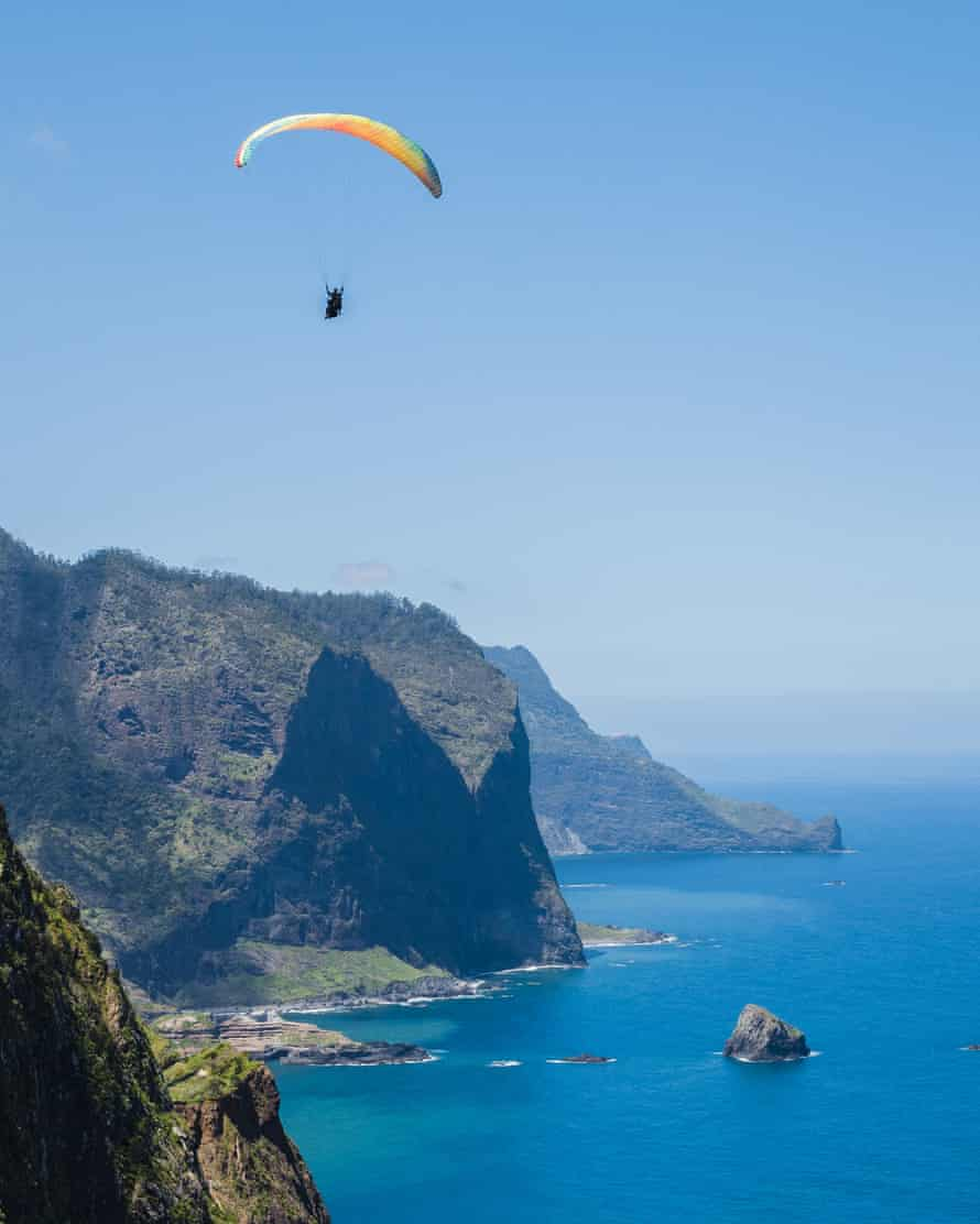Glimpse of the paraglider flying over the village of Porto da Cruz with the Penha D'aguia mountain in the background on the island of Madeira.