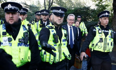 Police escort Michael Gove as he leaves parliament.