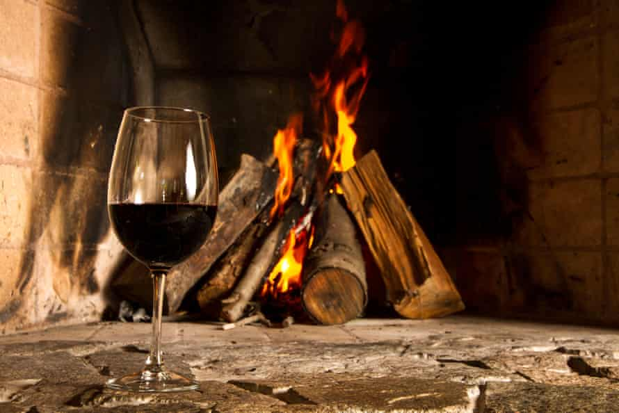 A glass of red wine in front of an open fire