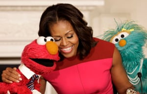 Michelle Obama with Sesame Street characters Elmo and Rosita after delivering remarks at the White House.