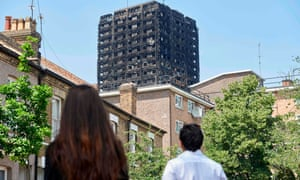 The burnt-out shell of Grenfell Tower is seen behind terraced houses.
