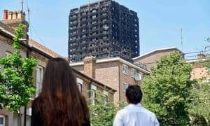 Local residents look up at the burnt Grenfell Tower block behind some terraced houses