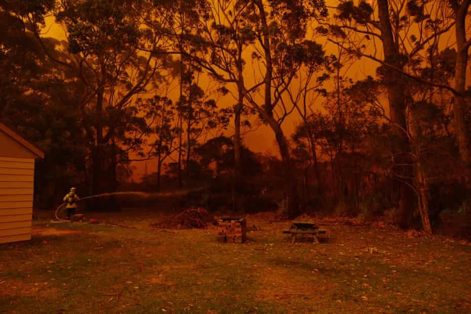 Firefighting crews battle a bushfire encroaching on properties near Lake Tabourie between Bateman's Bay and Ulladulla south of Sydney.