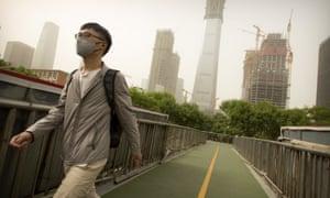 A man wears a face mask as he crosses a pedestrian bridge in Beijing.