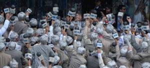Hawke surrounding by people in grey wigs