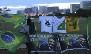 A man sells T-shirts and flags with the image of presidential frontrunner Jair Bolsonaro in front of the headquarters of the national congress, in Brasilia.