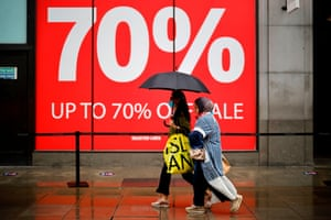 Shoppers shelter under an umbrella as they walk past sale signs in the rain on Oxford Street in London.