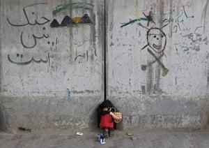 An Afghan girl who sells pens sleeps along a street in Kabul