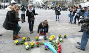 People leave messages and flowers in front of the stock exchange building in Brussels