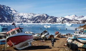 A man walks to his boat past boats in the town of Tasiilaq, Greenland